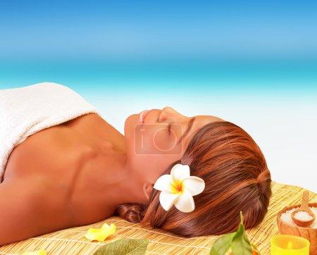 Photo pour Attrayante femme américaine dormant sur table de massage sur la plage, jouissant spa de jour été luxe voyager concept - image libre de droit