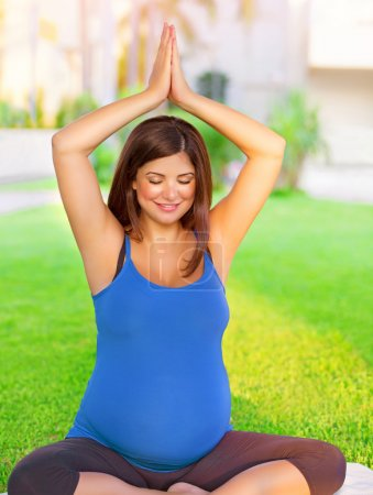 Pregnant woman engaged in yoga outdoors