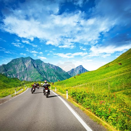 Photo for Group of motorcyclists on countryside in mountains, traveling along Alpine mountains, extreme sport, driving along cow pasture - Royalty Free Image