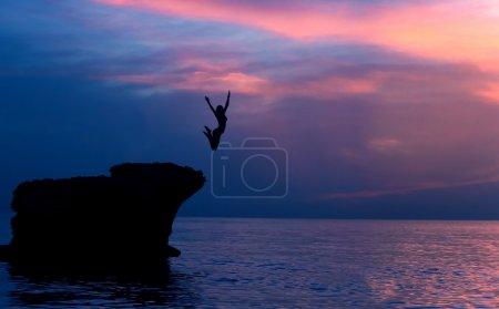 Foto de Chica valiente saltando de las rocas en la noche sobre hermoso fondo púrpura puesta de sol, aventura de verano, concepto de libertad - Imagen libre de derechos