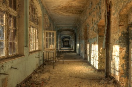 Abandoned hospital corridor with bed