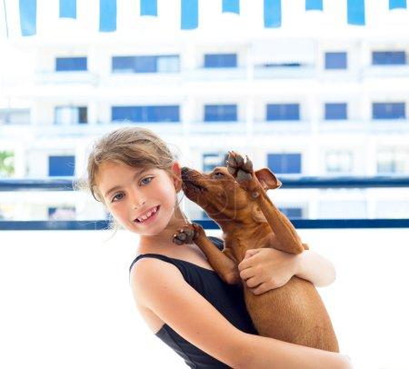 Photo pour Brunette enfant fille avec maillot de bain d'été jouer avec le chien dans l'appartement - image libre de droit