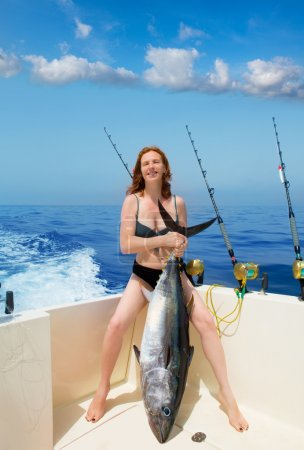 Bikini fisher woman holding bluefin tuna on boat