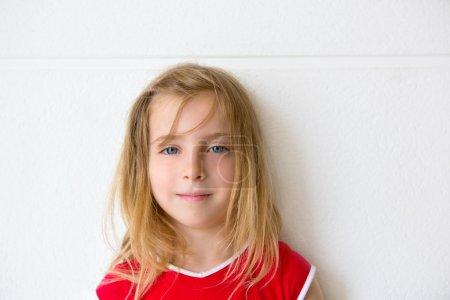 Photo pour Blonde belle gamine souriant sur un portrait mural blanc - image libre de droit