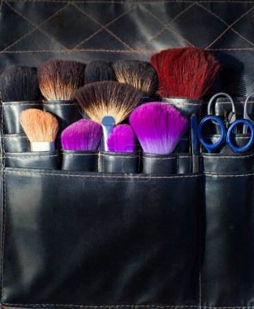 brushes scissors and tools of makeup artist in black
