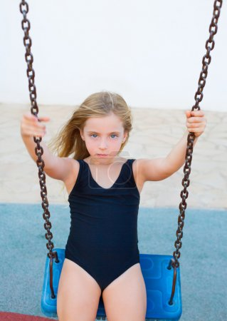 blond girl swinging on blue swing with swimsuit
