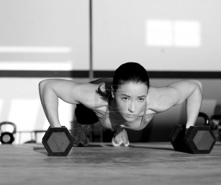 Photo for Gym woman push-up strength pushup exercise with dumbbell in a crossfit workout - Royalty Free Image