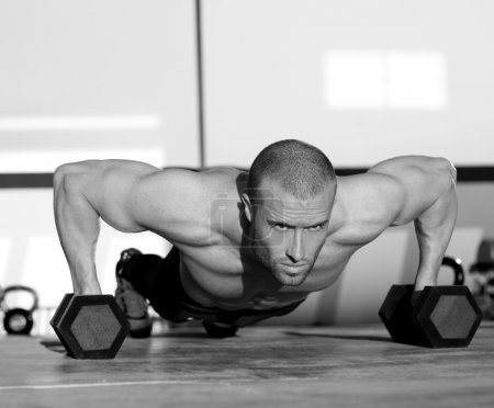Photo for Gym man push-up strength pushup exercise with dumbbell in a crossfit workout - Royalty Free Image