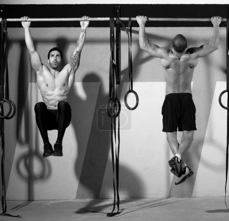Photo for Crossfit toes to bar men pull-ups 2 bars workout exercise at gym - Royalty Free Image