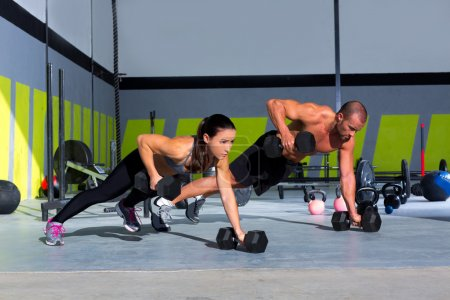 Photo for Gym man and woman push-up strength pushup with dumbbell in a crossfit workout - Royalty Free Image