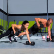 Gym man and woman push-up strength pushup with dum...