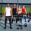 Gym group with weight lifting bar workout in cross...