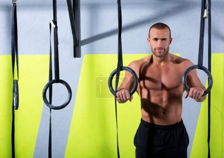 Photo for Crossfit dip ring man relaxed after workout at gym dipping exercise - Royalty Free Image