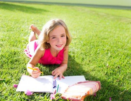 child kid girl doing homework smiling happy on grass