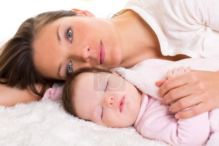 Photo for Baby girl sleeping with mother care near on white fur - Royalty Free Image