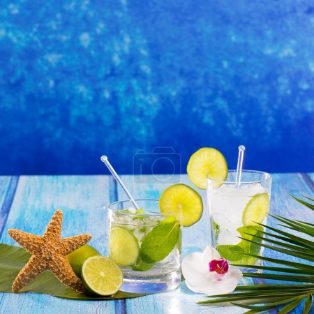 Photo for Cuban Mojito cocktail in tropical blue wood with flowers and starfish - Royalty Free Image