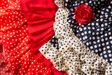 Photo for Flamenco dresses in red and blue with spot with red rose typical from Spain Espana - Royalty Free Image