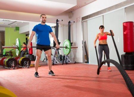 Crossfit gym weight lifting bar man woman battling ropes