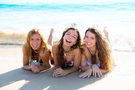 Happy three friends girls lying on beach sand smiling