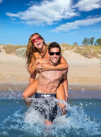 Teen couple enjoying piggyback on summer beach