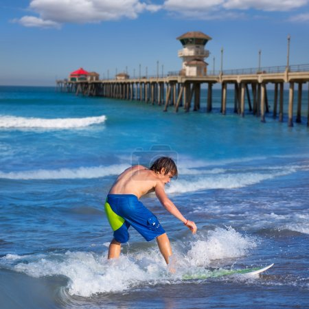 Boy surfer surfing waves on Huntington beach
