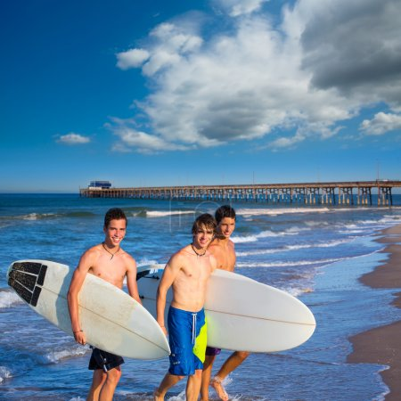 Boys surfers group coming out from beach
