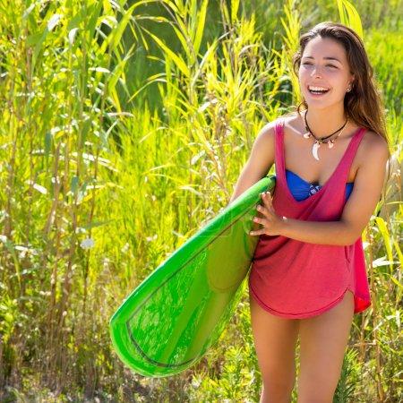 Brunette surfer girl walking in the jungle