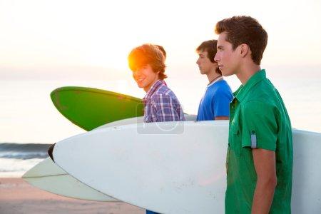Surfer teen boys walking at beach shore