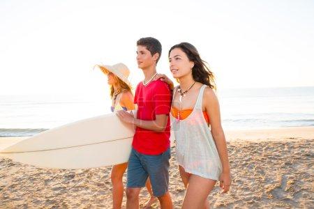 Surfer girls with teen boy walking on beach shore
