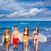 Chlapci a dívky teen surfařů, které vyplynuly z pláže