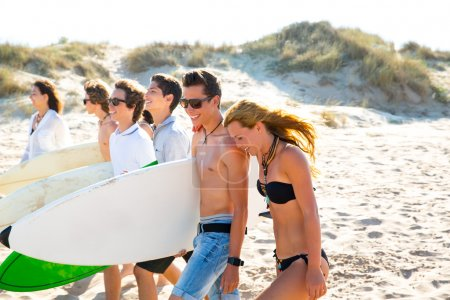 Surfer teen boys and girls group walking on beach