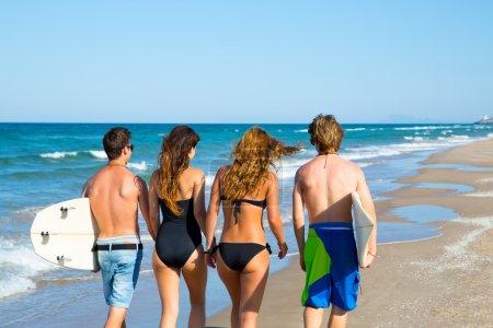 Photo pour Adolescents surfeurs groupe de garçons et filles marchant vue arrière sur la plage - image libre de droit