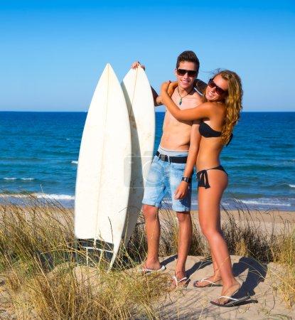 Teen surfers couple hug on the beach