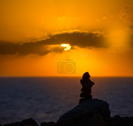 Stacked stones for a wish on Mediterranean sunset