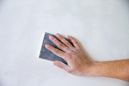 plastering man hand sanding the plaster