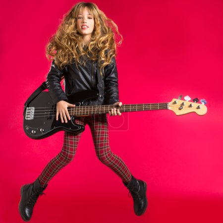 Photo pour Blond Rock and roll fille sautant jouer de la guitare basse sur fond rouge - image libre de droit
