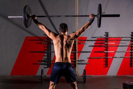 Photo pour Haltère haltérophilie homme vue arrière entraînement exercice à la boîte de gym - image libre de droit