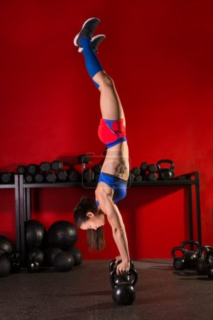 kettlebell handstand woman workout in red gym