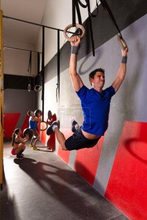 Muscle ups rings man swinging workout at gym
