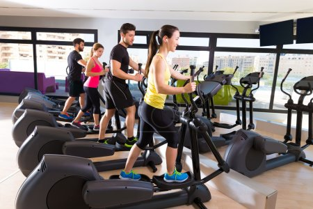 Photo for Aerobics elliptical walker trainer group at fitness gym workout - Royalty Free Image