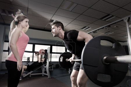 Photo for Couple at gym weightlifting workout barbell and dumbbell fitness - Royalty Free Image