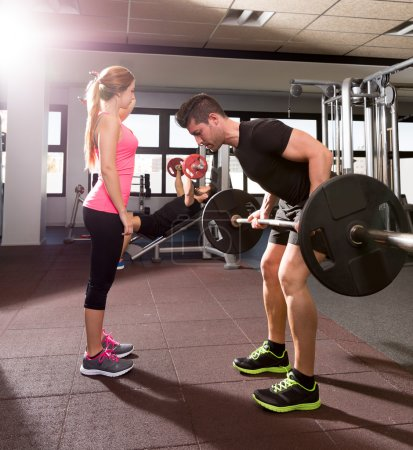 Gym weightlifting couple workout barbell dumbbell