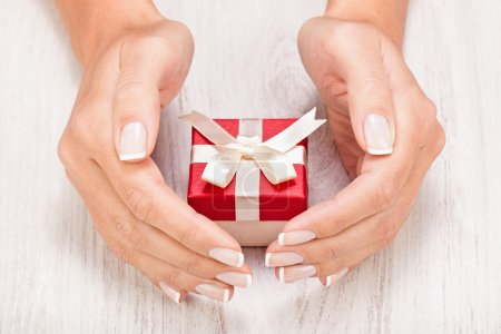 Photo for Red small gift covered with female hands - Royalty Free Image