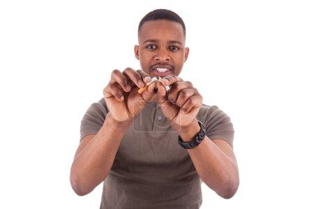 Photo pour Jeune homme afro-américain brisant une cigarette, isolé sur fond blanc - image libre de droit