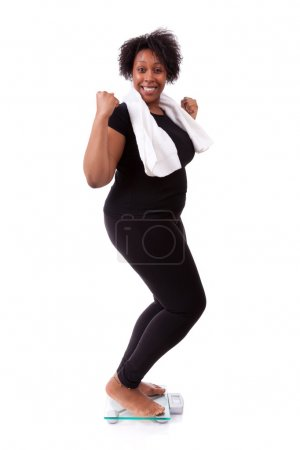 African American woman cheering on scale - African