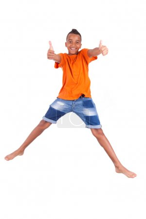Portrait of a cute teenage black boy jumping over white backgrou