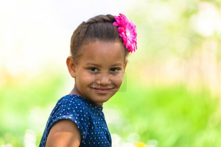 Photo for Outdoor portrait of a cute young black girl  lying down on the grass and smiling - African people - Royalty Free Image