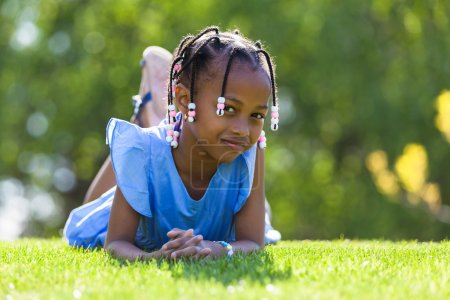 Outdoor portrait of a cute young black girl  lying down on the g