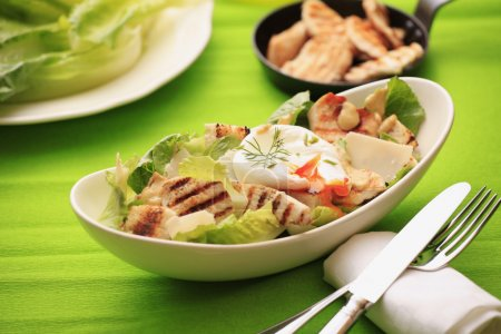 Photo for Chicken Caesar salad with poached egg, grilled chicken, lettuce, croutons caesar dressing - Royalty Free Image