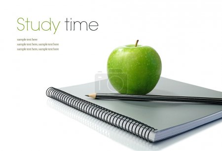 Studio macro of shiny green apple, pencil and new notebook on a white surface. Copy space.